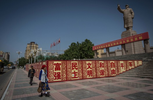 A Uighur woman walking past a statue of Mao Zedong in Kashgar City, northwestern Xinjiang, China, 2017. Photo credit: Guillaume Payen / SOPA Images / LightRocket via Getty Images.